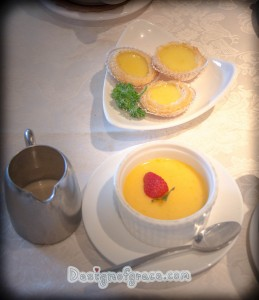 The desert displayed on the table with the 3 egg tarts on the plate on top and the mango pudding on the bottom of it