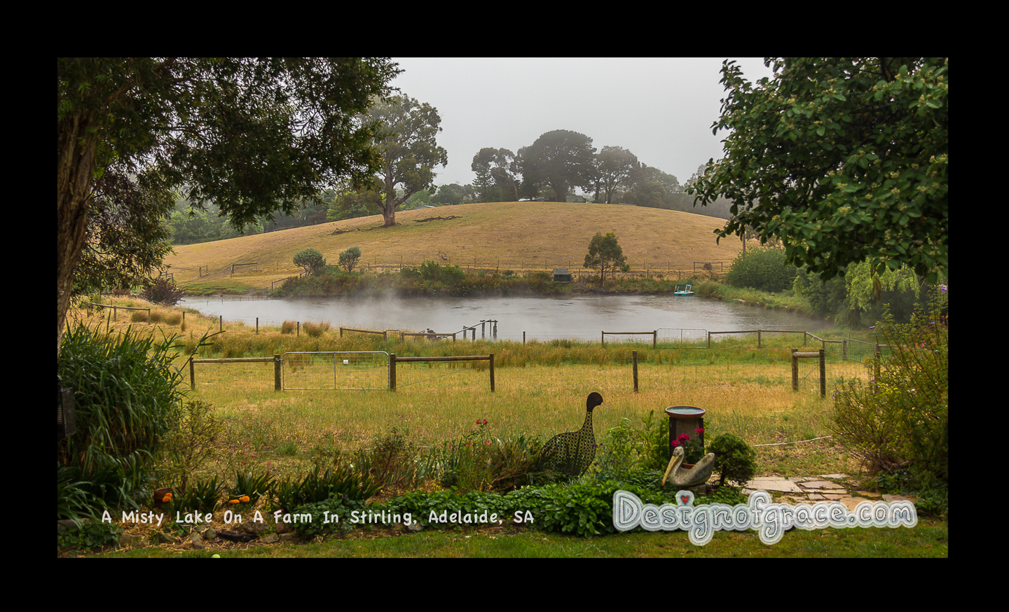 Misty scene in the Adelaide hills with a hill in the back with garden ornament in the foreground and a lake in the middle