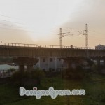 Sun setting over bridge like infrastructure with buildings below