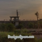 sun setting on the right with a station on the left and vegetation in the foregrouind
