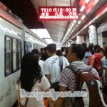 train on the left with a crowd of people on the right arriving in Guangzhou