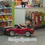 A little boy in a cool red toy car outside a shop