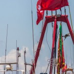 A close up of a Chinese boat and a bird of prey flying in between one of the poles