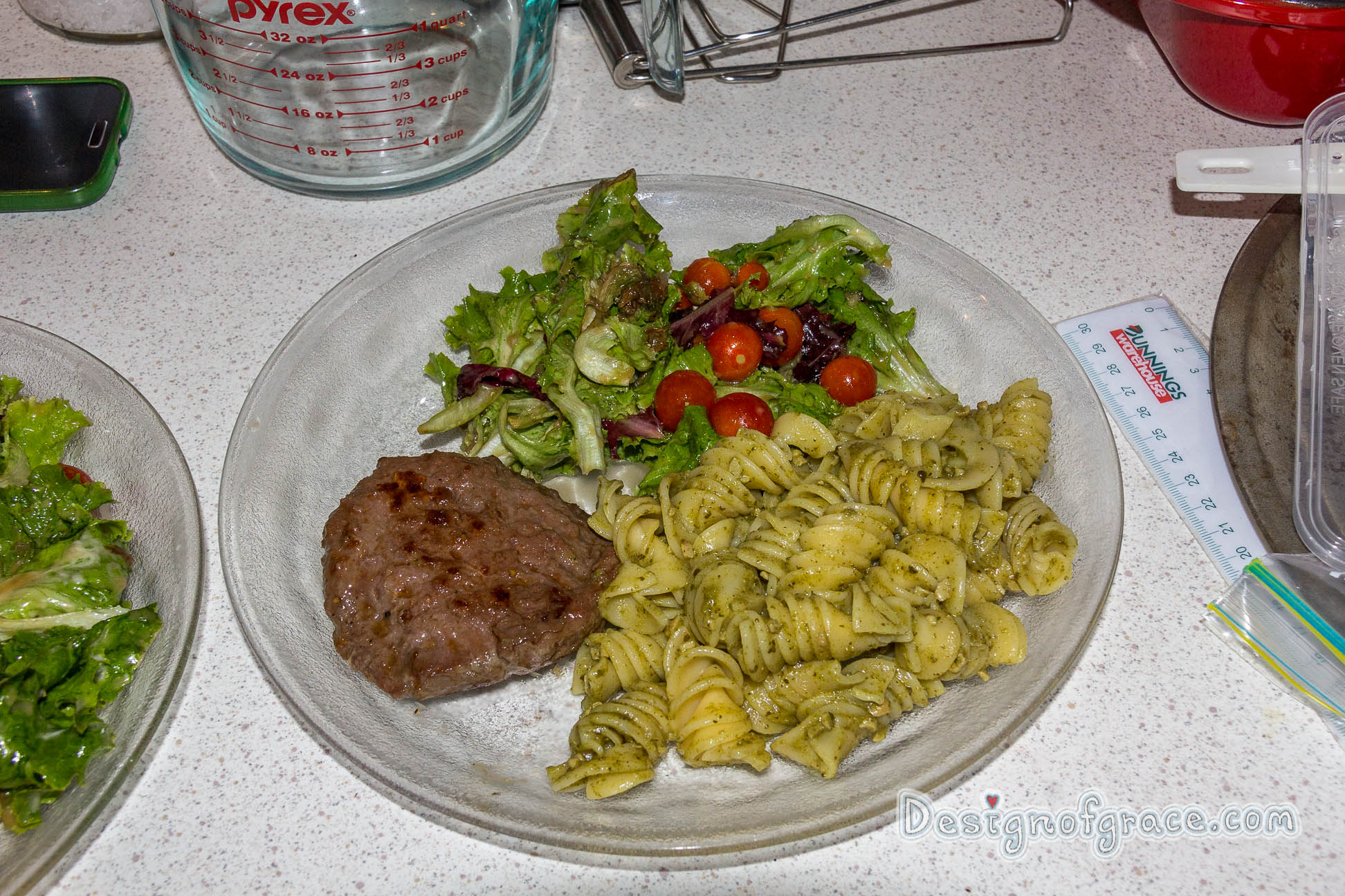 a plate of food with a kangaroo patty on the left which has been nicely browned with pesto pasta on the right and the home grown green and red lettuce and cherry tomatoes on top of the plate