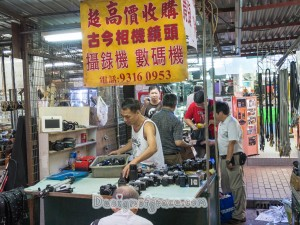 a guy behind his stall selling cameras which are laid on the table in front of him