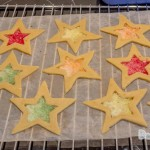 A tray of star cookies with the middle hollowed out in a star shape filled with colouful lollies unbaked