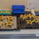 An overview of the two tray of baked star cookies with the middle hollowed out in a star shape filled with colouful lollies baked