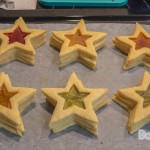 A tray of baked star cookies with the middle hollowed out in a star shape filled with colouful lollies baked