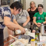 Elizabeth the presenter measuring ingredients and putting it in the mixing bowl with workshop participants watching