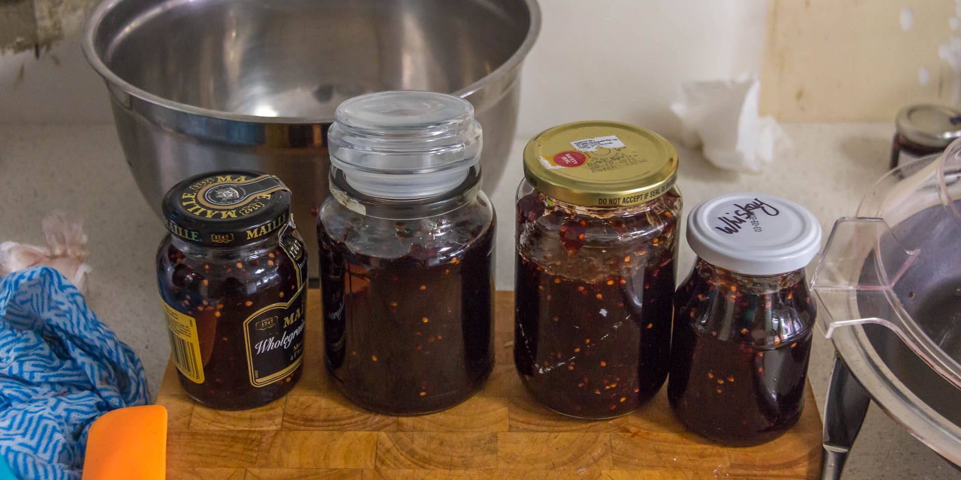 4 jars of mulberry jam on a wooden cutting board