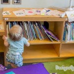A baby using the bookshelf to stand up to reach the finished buntings