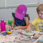 a girl with a pink cap on the left and a boy in a yellow shirt both busy drawing on their bunting