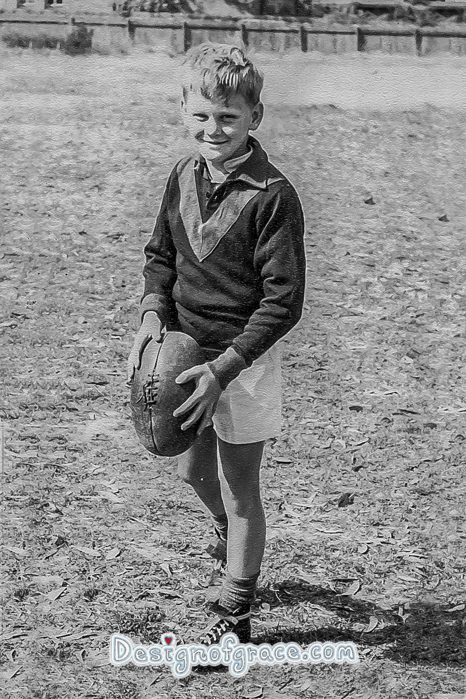 old black and white photo of a boy holding a football