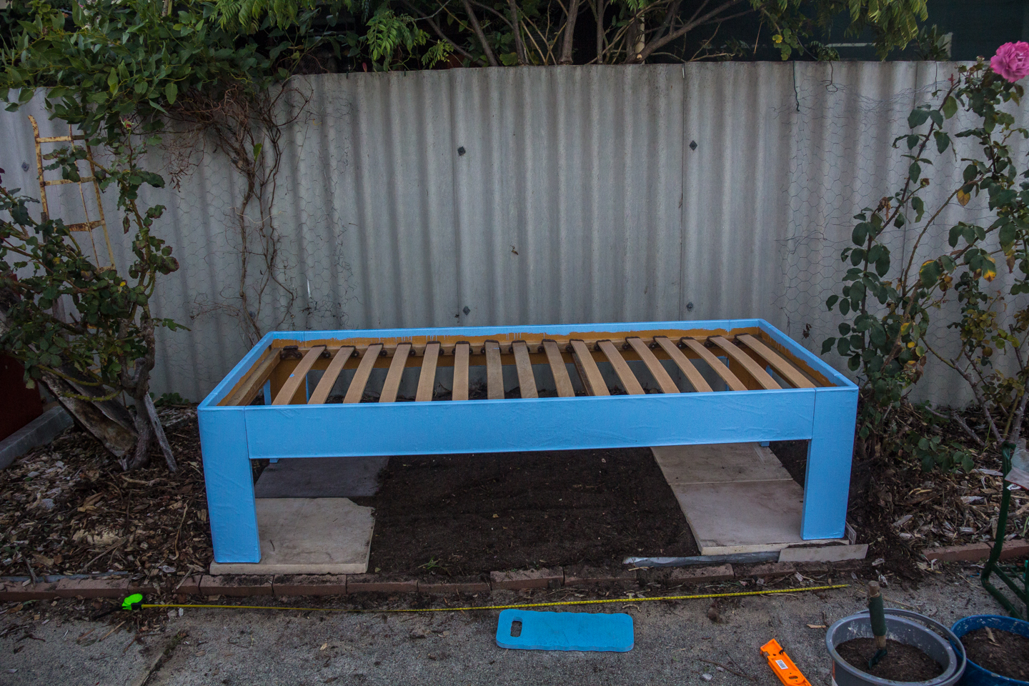 Bed frame on top of the pavement.