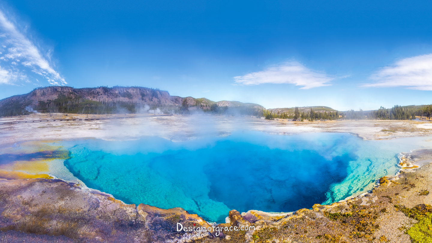 beautiful sapphire pool with mist on top with mountains in the background with blue skies