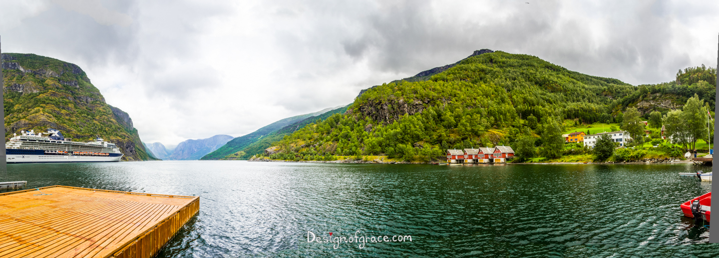 mountains and the Flåm fjord with a jetty on the left and red little houses on the right on the water.