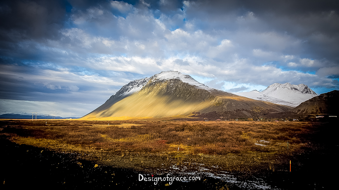 A lone snow capped mountain with interesting sun pattern on it and dramatic clouds