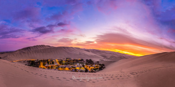 Orange and purple skiles at sunset with the city of huacachina with lights lit up