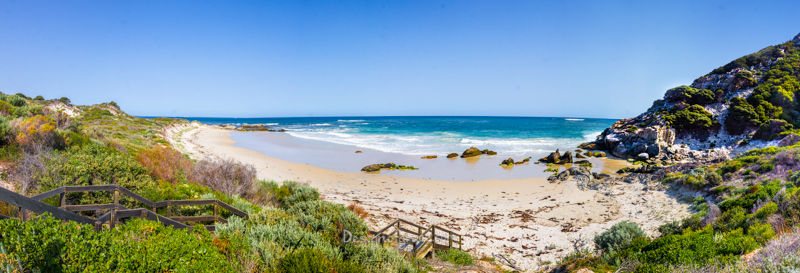 A beautiful panorama of barren's beach. With green bushes on the left with a stairs leading down to the beach. The blue ocean and yellow sand beach in the middle with rocky hills on the right with green bush growing on the hill