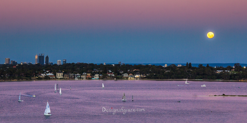 Beautiful purple, pink and blue sunset with the super blue moon on the right above Perth city on the left with yachts sailing in the water in the foreground