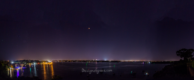 A panorama of the actual size of the semi eclipse with the city lights below