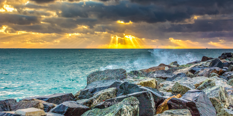 Sunset at Cottesloe over the Indian Ocean with sun rays beaming out of dark and dramatic clouds with colourful rocks on the right