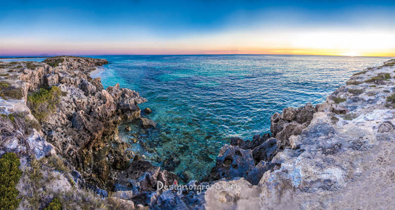 beautiful and colourful sunset with turquoise waters with dark contrastic rocks with lots of textures