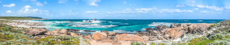 Redgate Beach Panorama, Margaret River, Western Australia with beautiful blue sky with clouds and waves crashing on the rocks with greenery around.