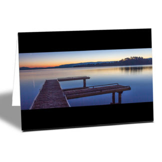 Still waters at Flathead Lake Jetty at sunset with orange and blue colours horizontal card