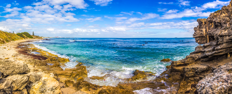 blue skies with Beautiful waves for surfing at the Cove on the left juxtapose with brown rocks on the right, Cottesloe, Western Australia