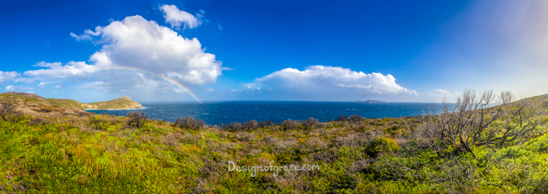 The blowholes rainbow panorama, Albany, WA with blue skies and a bit a white fluffy clouds. Green bush on the bottom