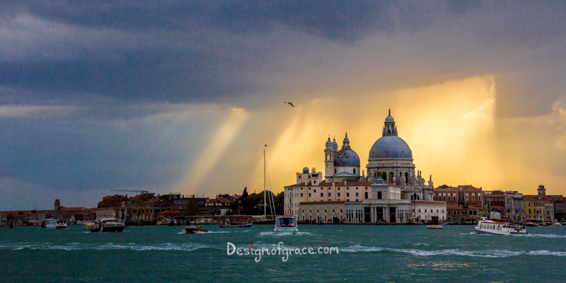 santa maria della salute sunset with orange sun rays shinning through the dark rain clouds, venice