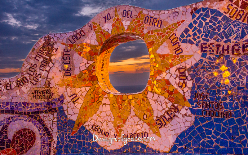 Looking through the Parque De Amor mosaic bench of a sun, Miraflores, Lima, Peru at Sunset with orange and purple hues