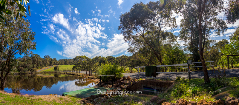 beautiful peaceful Meelup Brook panorama with beautiful blue skies and patches of clouds with still waters reflecting the surroundings and green trees on the left, Eagle Bay, Western Australia