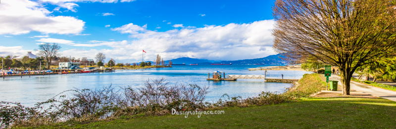 Beautiful sunny day at English Bay Beach Panorama with blue skies and white fluffy clouds, Vancouver, Canada