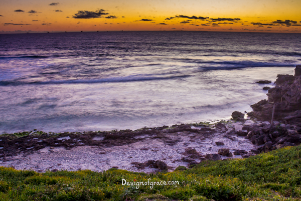 Beautiful orange Sunset with ships on the horizon with sand and rocks on the bottom with greenery at the Sundial, Cottesloe, Western Australia